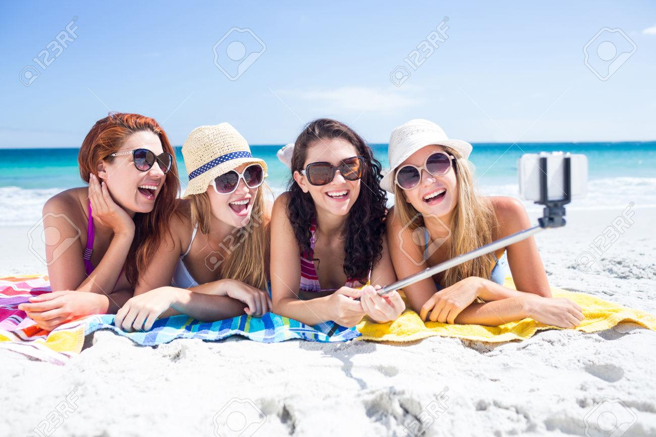 44772499-Happy-friends-wearing-sun-glasses-and-taking-selfie-at-the-beach-Stock-Photo